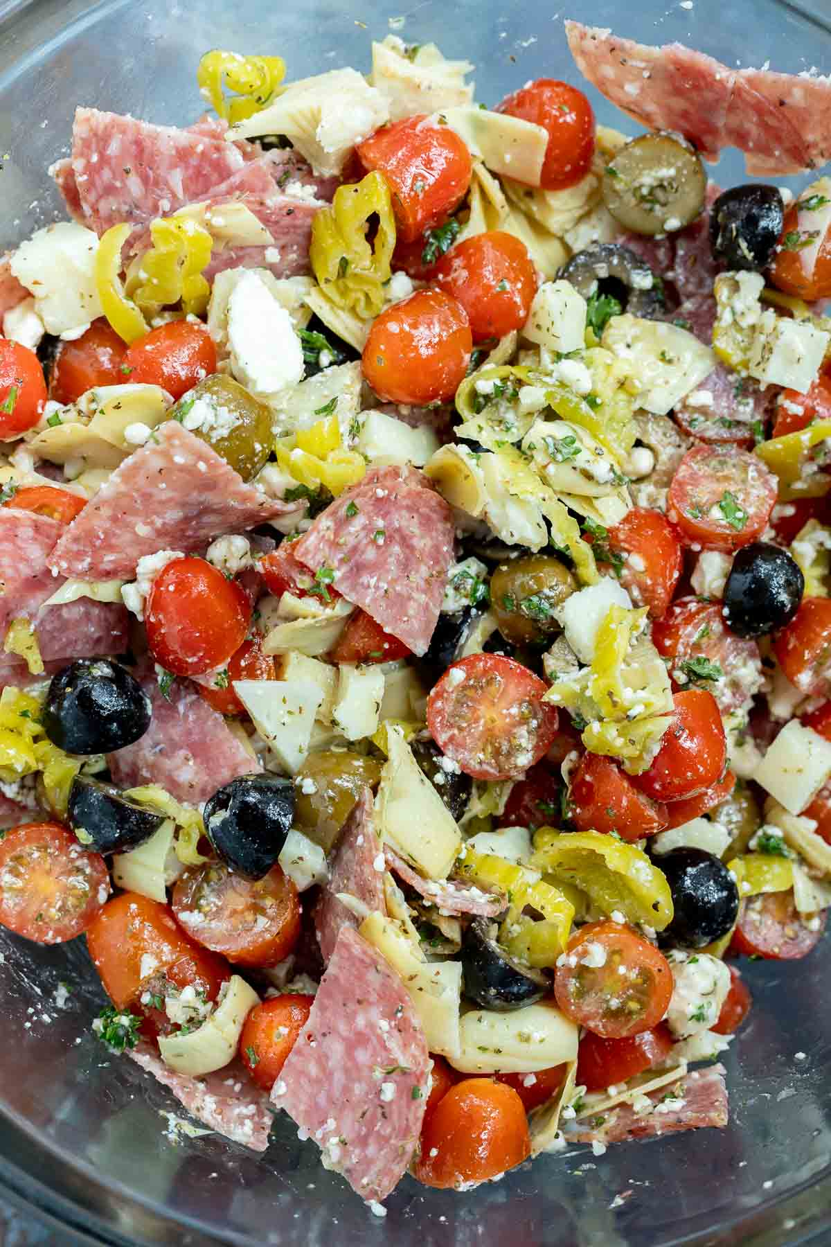 salami, olives, tomatoes, artichokes and pepperonis in glass mixing bowl
