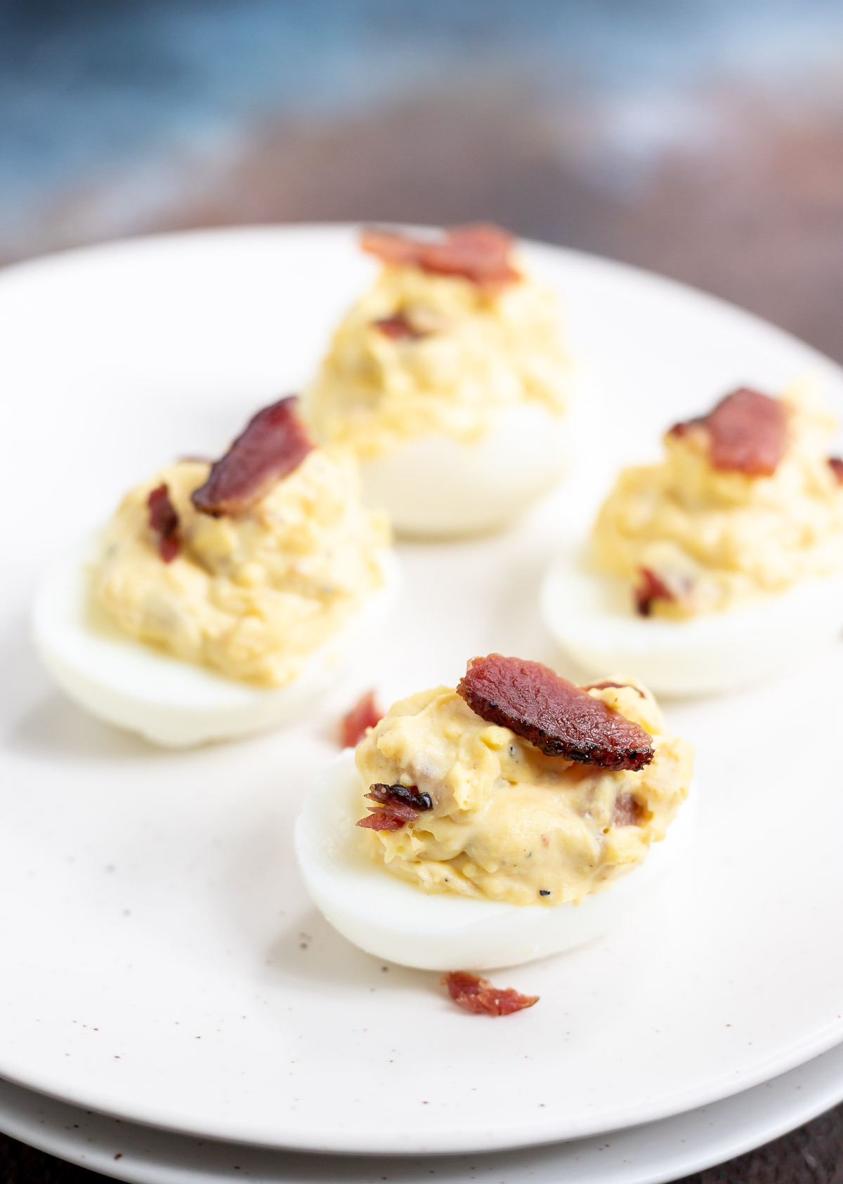 deviled eggs topped with bacon on white plate