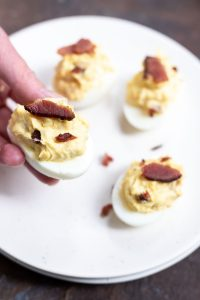 hand holding bacon deviled egg