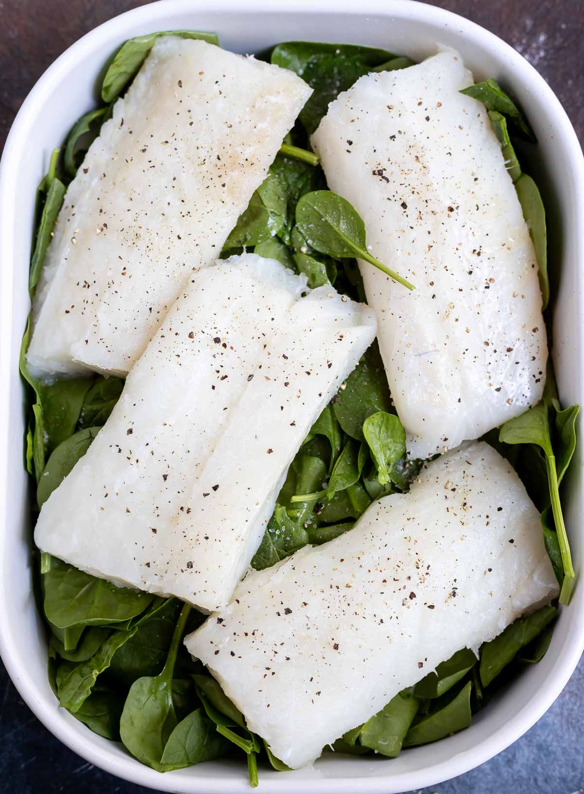 raw cod on top of fresh spinach