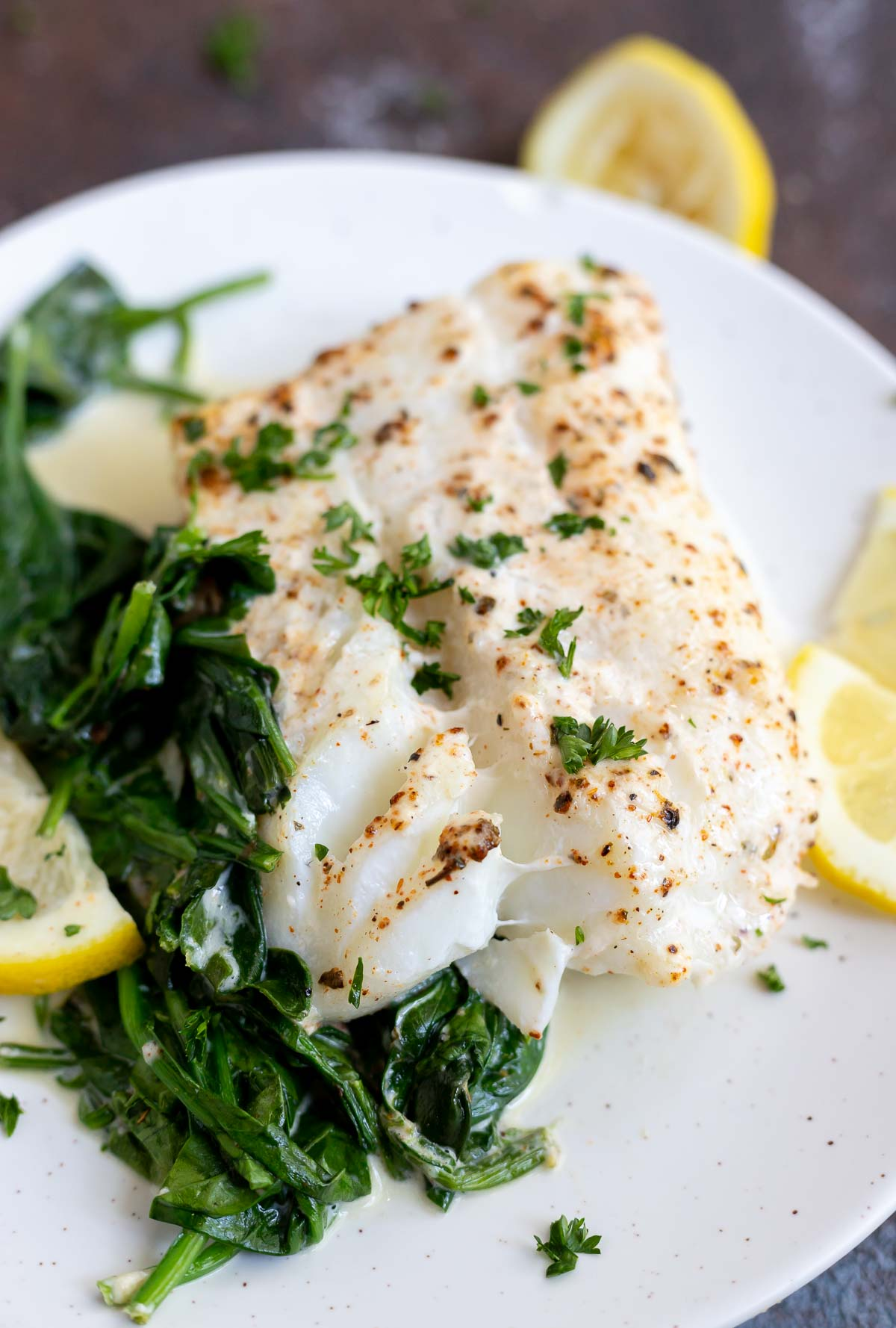 cod, spinach and cream served on white plate
