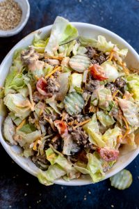 lettuce, burger, shredded cheese, pickles and tomatoes in white bowl