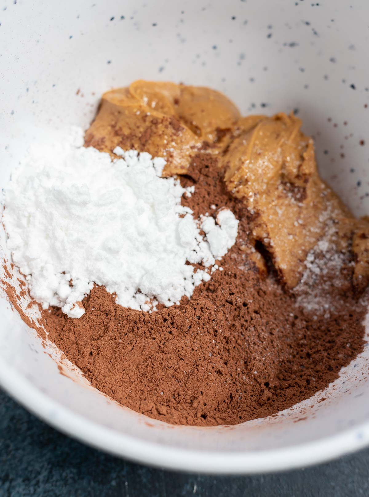 ingredients for chocolate peanut butter balls in white bowl