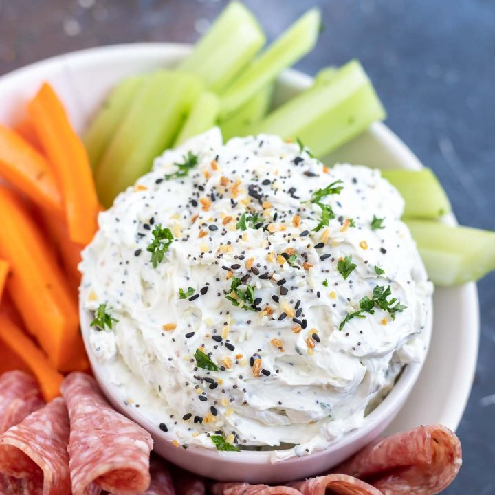 prepared dip served on a white plate with veggies and salami