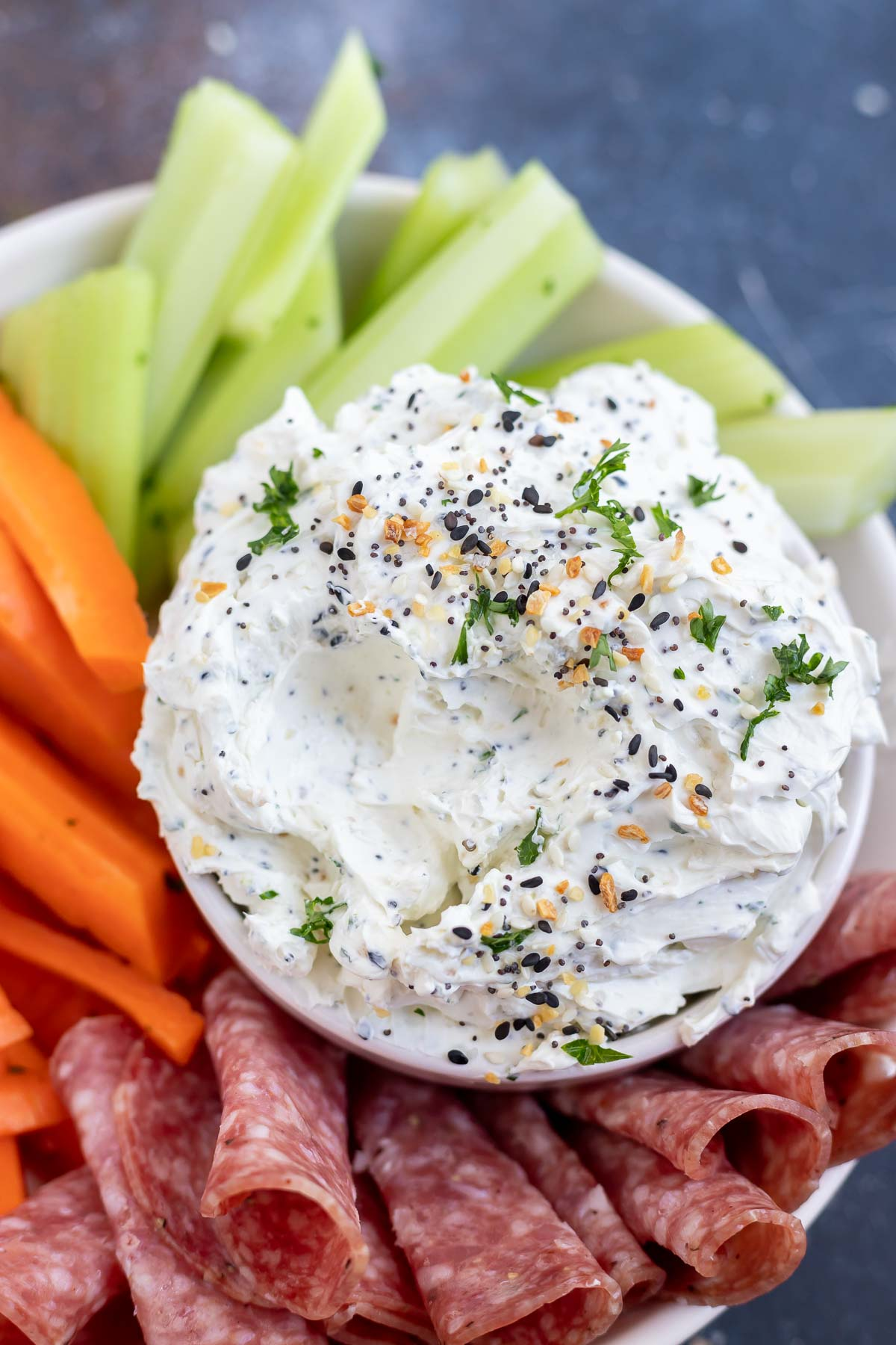 cream cheese dip topped with bagel seasoning and parsley surrounded by veggies