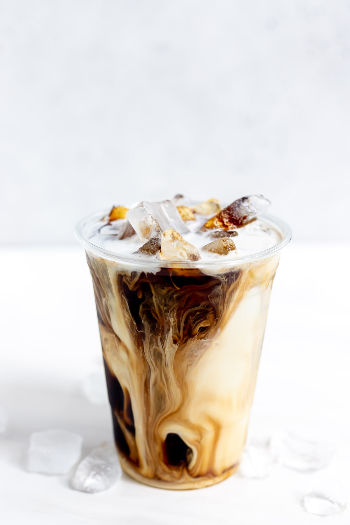 clear plastic cup filled with ice, black coffee and cream