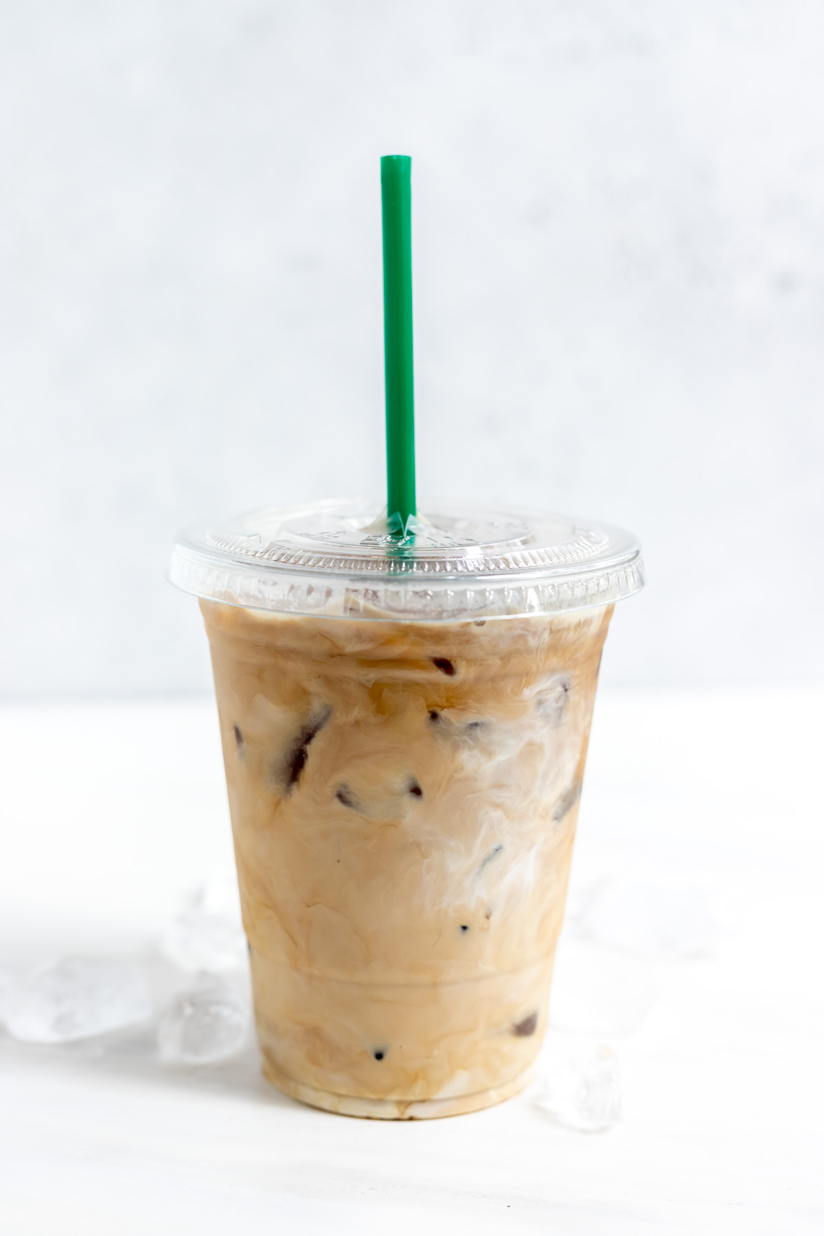 creamy iced coffee in clear plastic cup with green straw