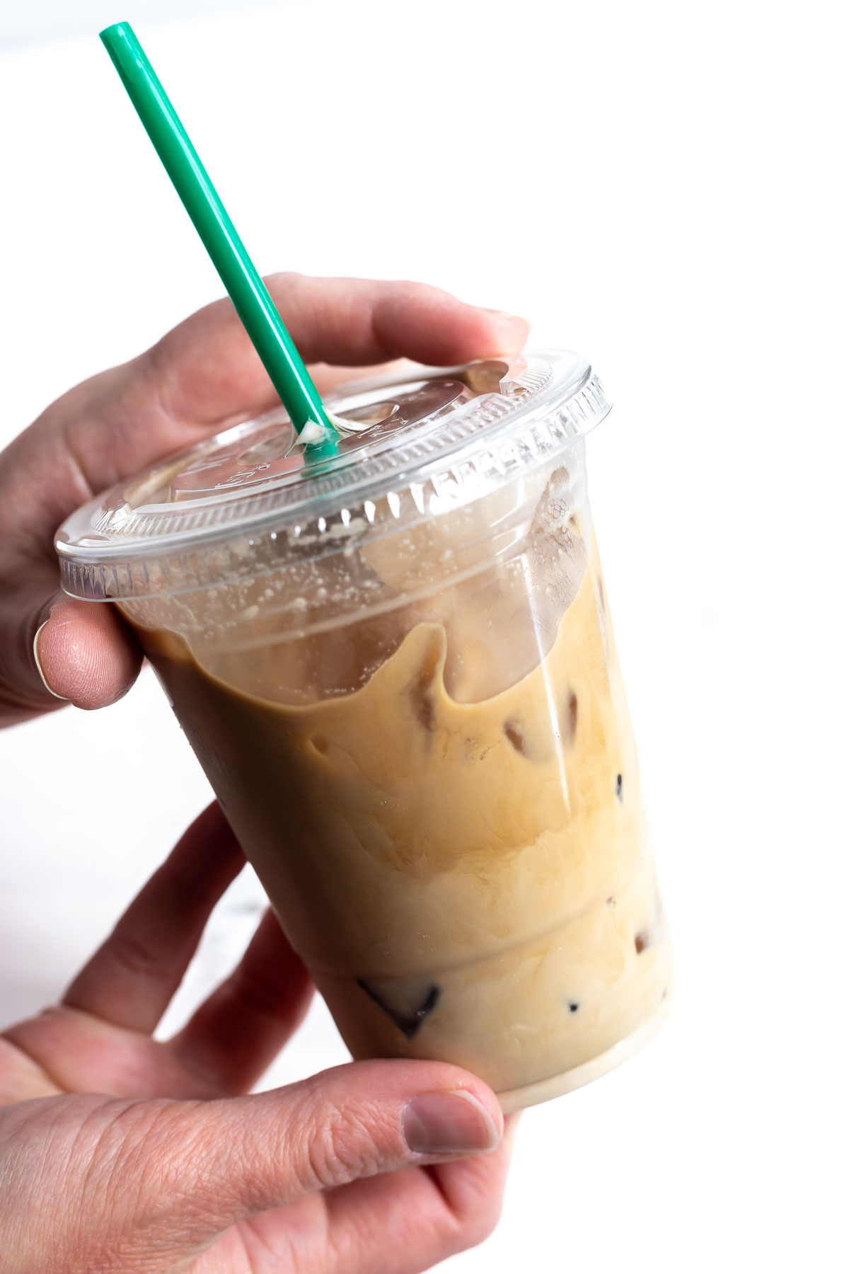hands holding plastic cup filled with iced coffee
