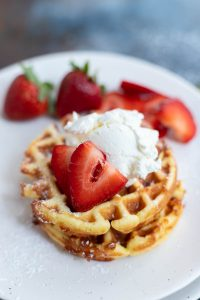 strawberry cream waffles on white plate