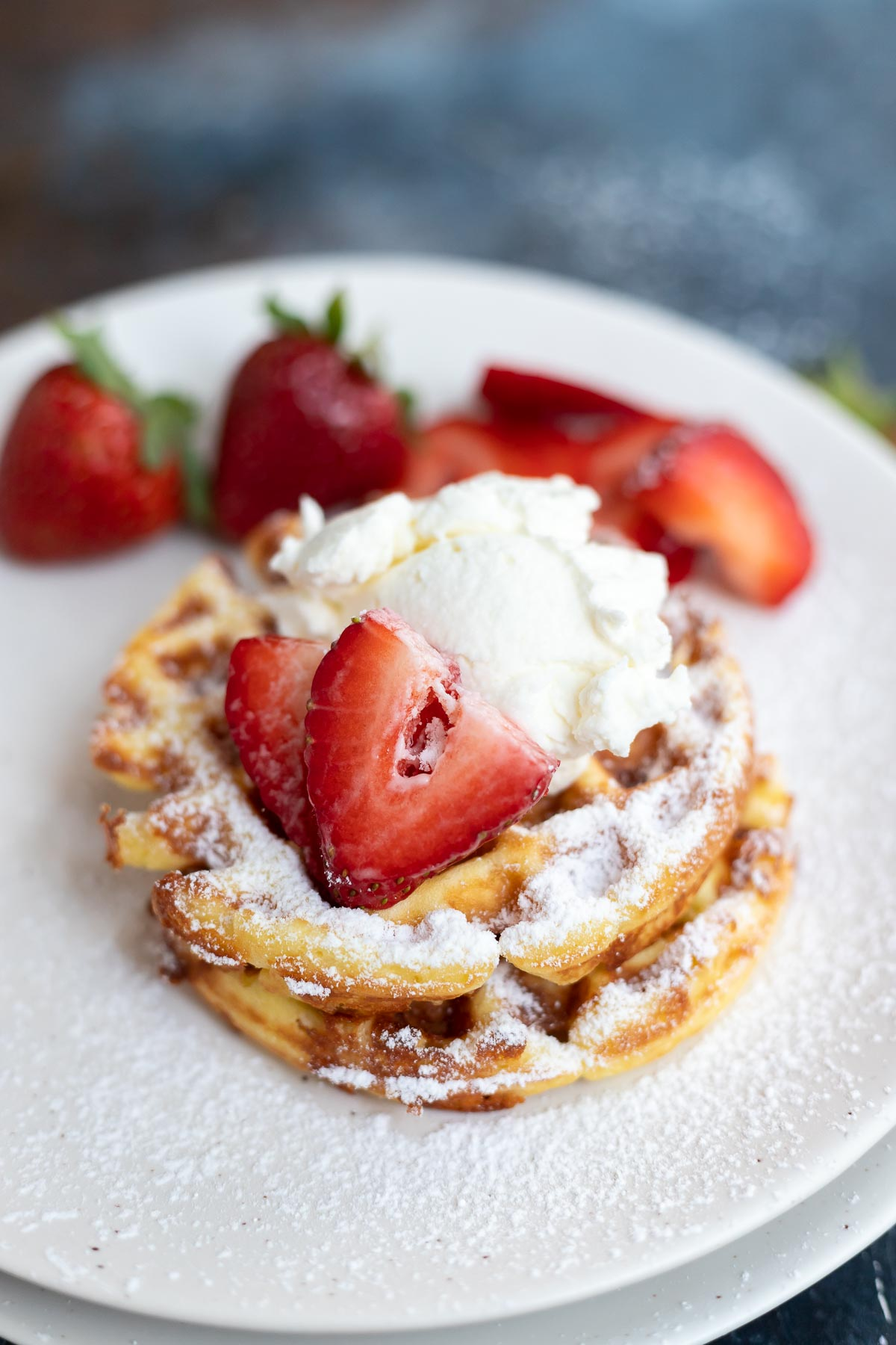 two low carb waffles topped with powdered sugar, strawberries and cream