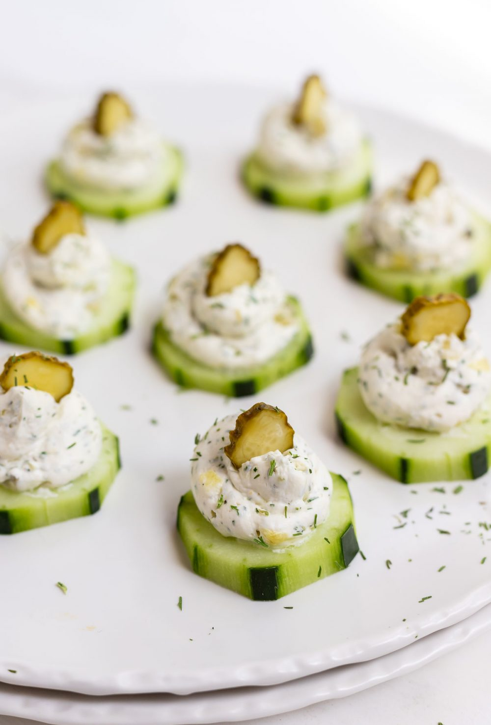cucumber pickle bites served on white platter