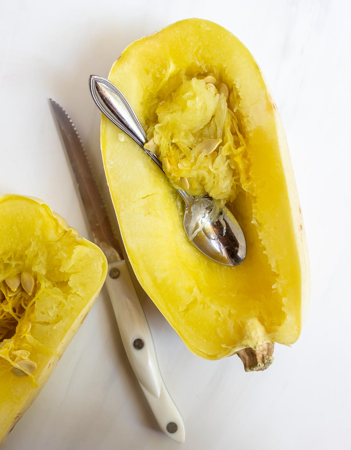 cooked spaghetti squash with silver spoon to scoop out seeds