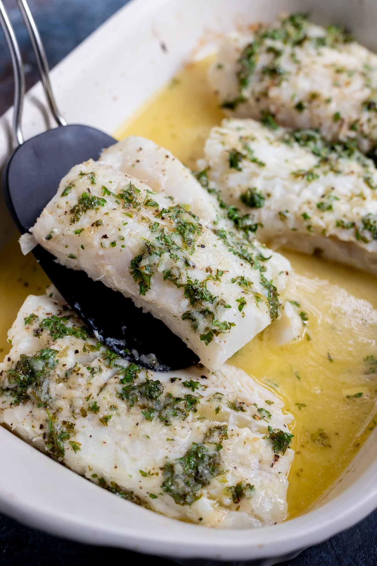 black spatula lifting baked cod fillet out of white roasting dish