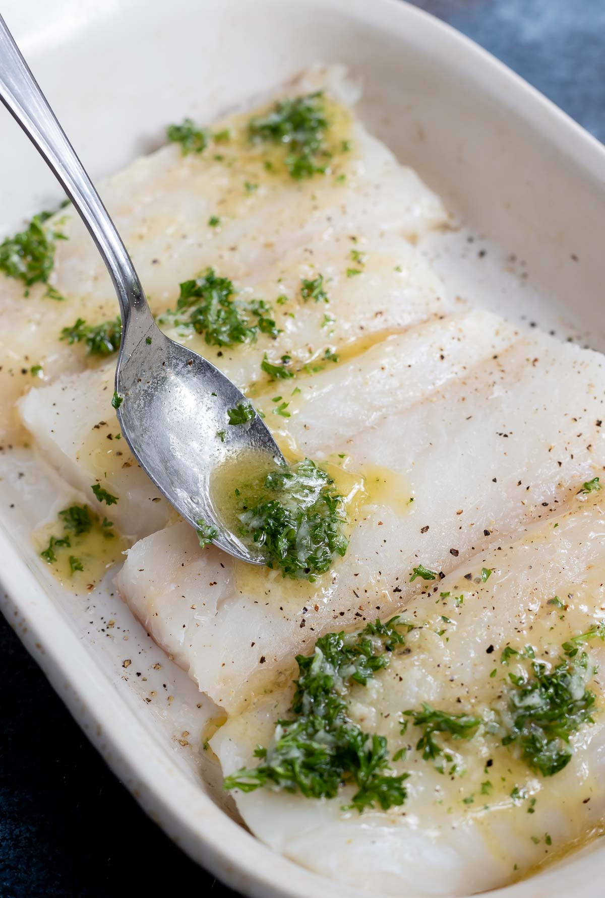 raw cod fillets in white roasting dish with spoon drizzling melted butter and parsley on top