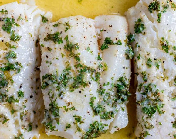 baked cod topped with herbs sitting in melted butter