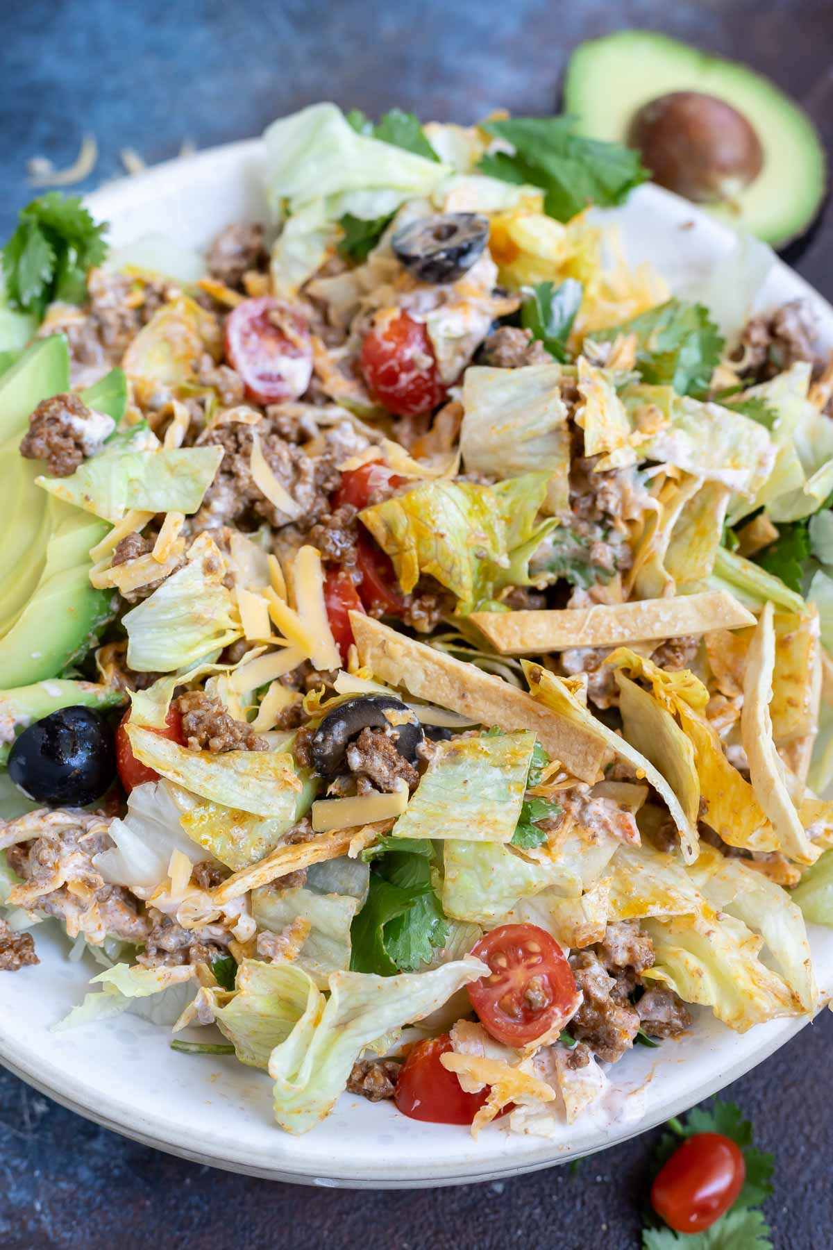 taco salad ingredients all mixed together in white bowl