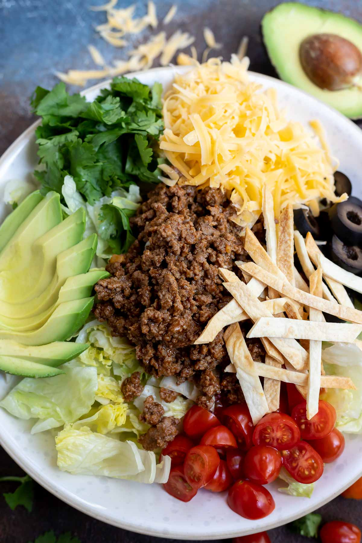taco salad ingredients arranged in white bowl, not yet mixed
