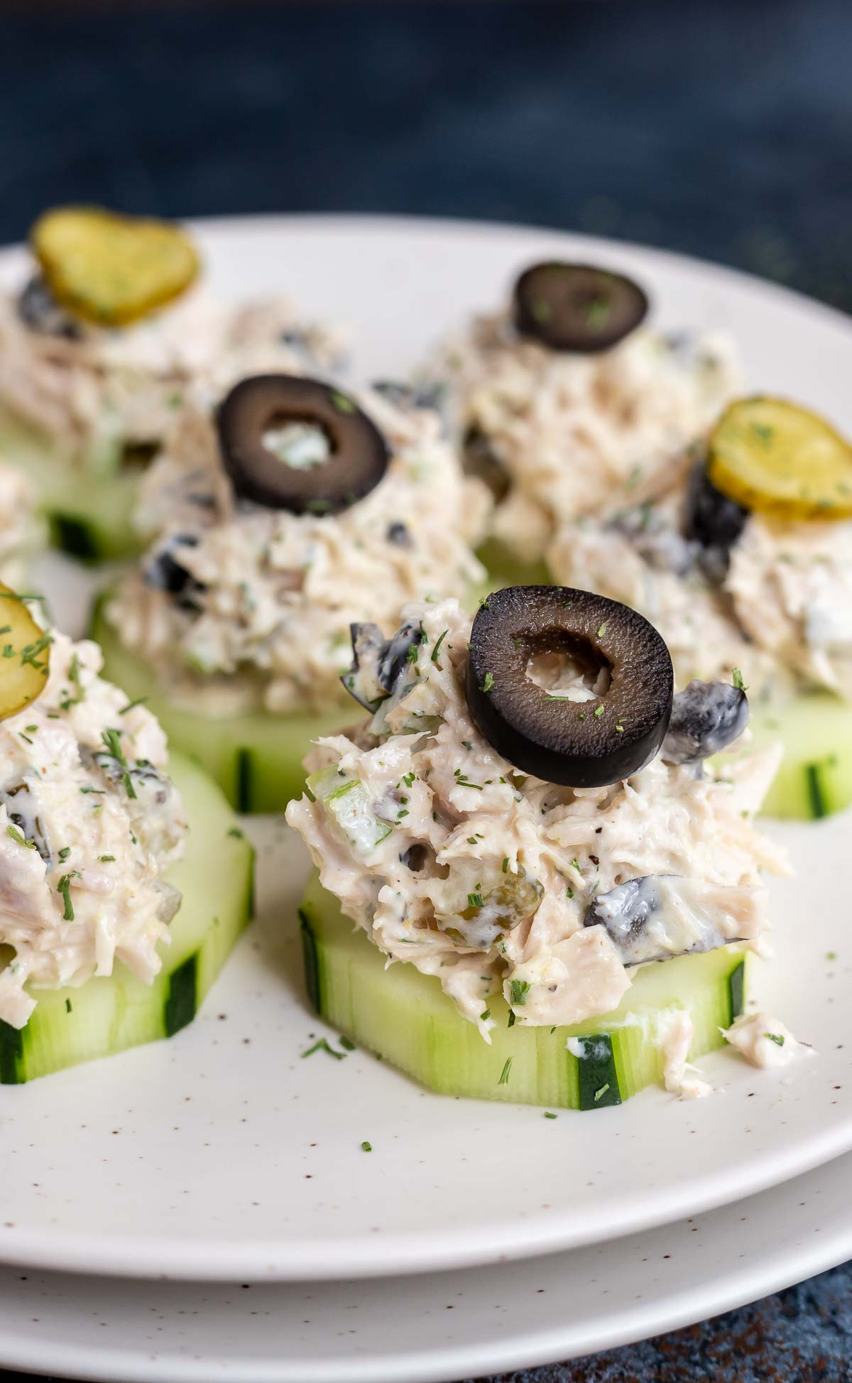 sliced cucumbers topped with tuna salad and a sliced black olive