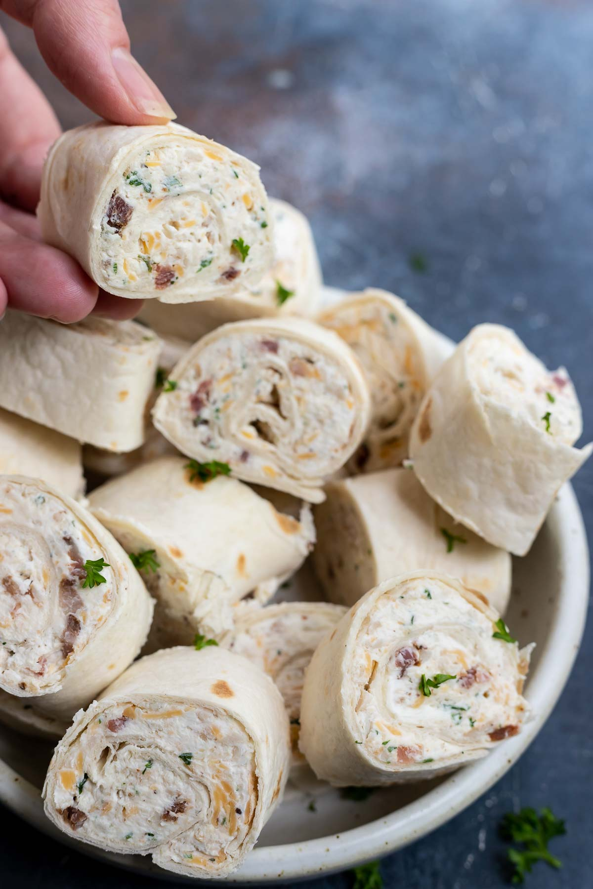 hand grabbing tortilla roll up from white plate