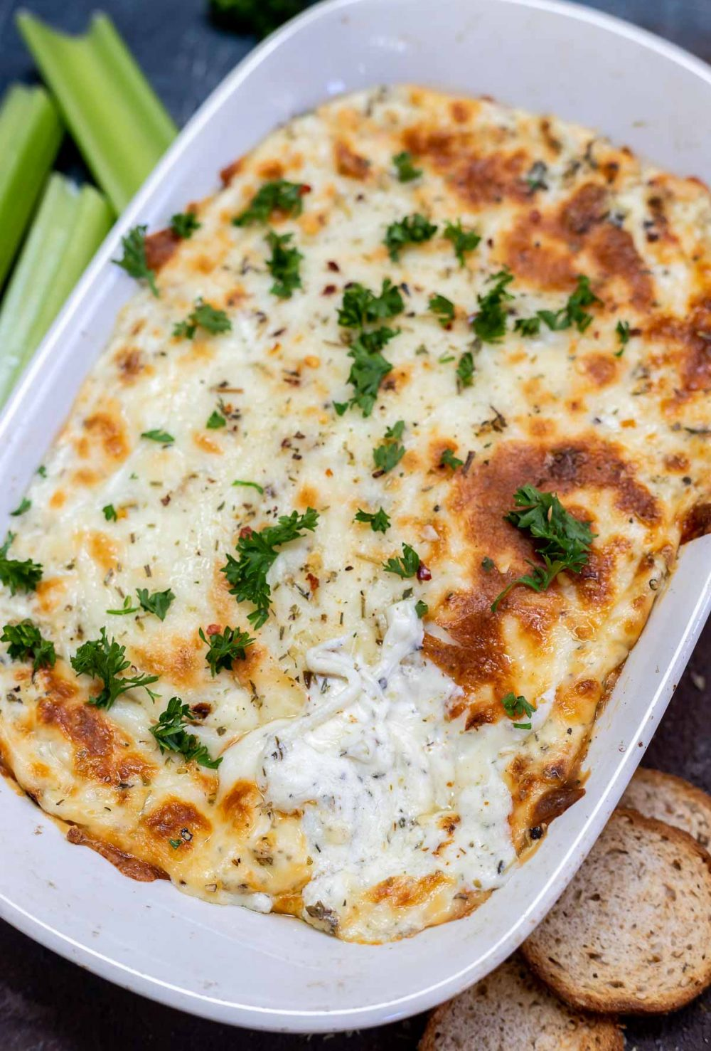 melty cheese dip topped with chopped parsley in white serving dish