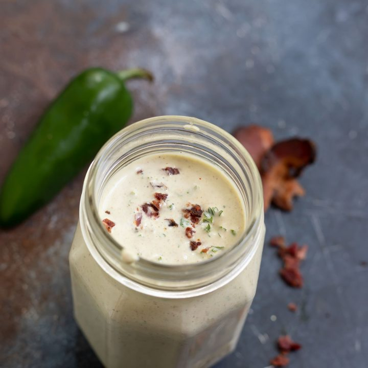 creamy dressing topped with bacon crumbles in clear glass jar