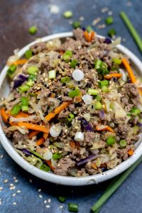 egg roll bowl ingredients topped with green onions in white bowl