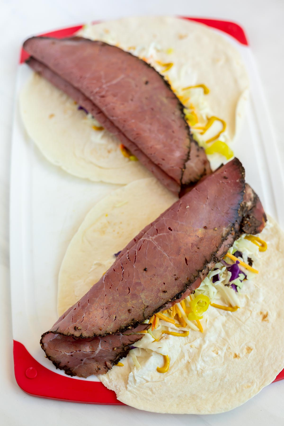 two flat tortillas topped with cheese, cabbage and pastrami on cutting board
