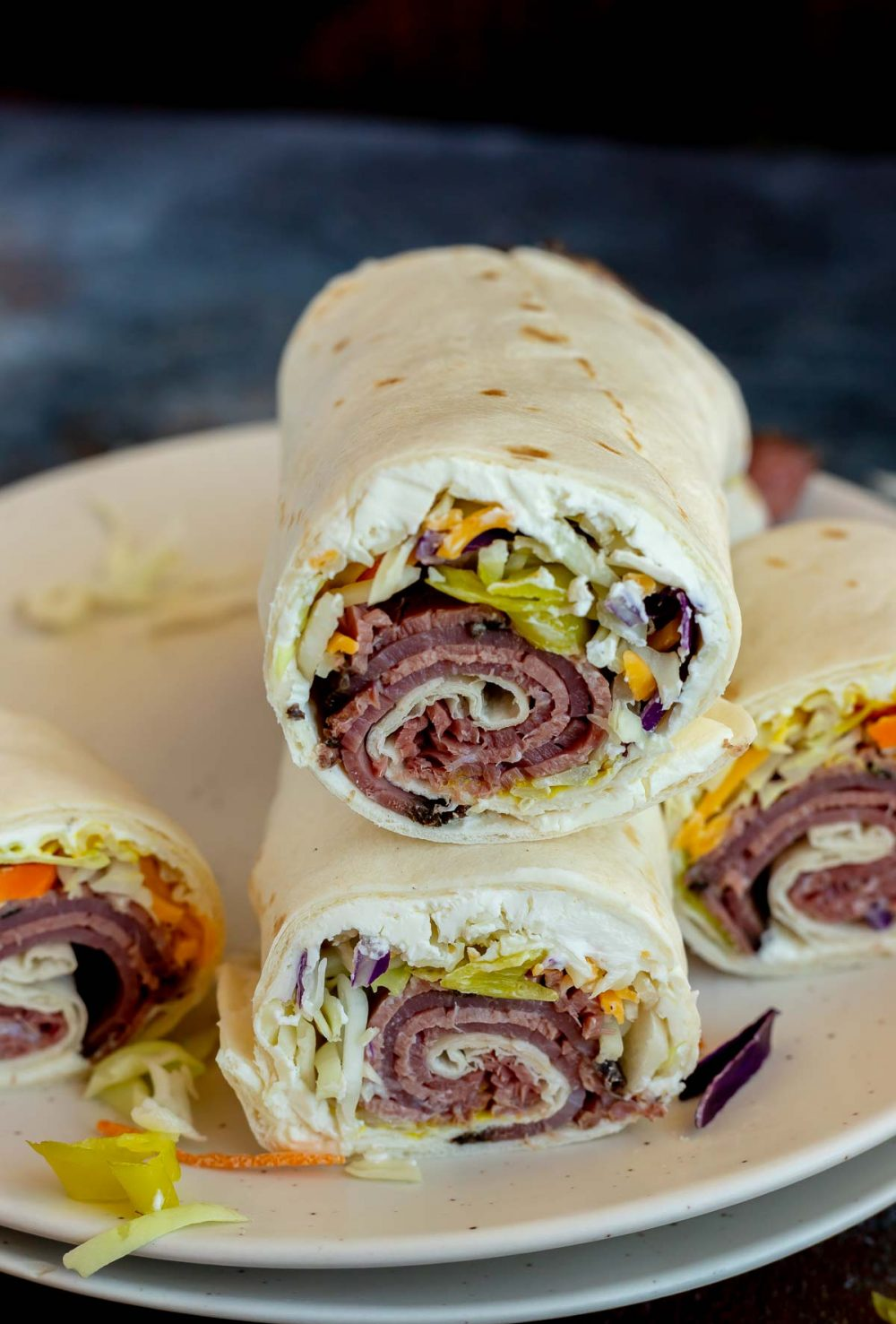 two pastrami tortilla rolls stacked on white plate