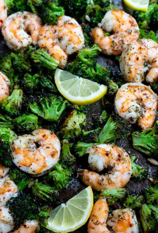 cooked shrimp and broccoli with lemon slices on baking sheet