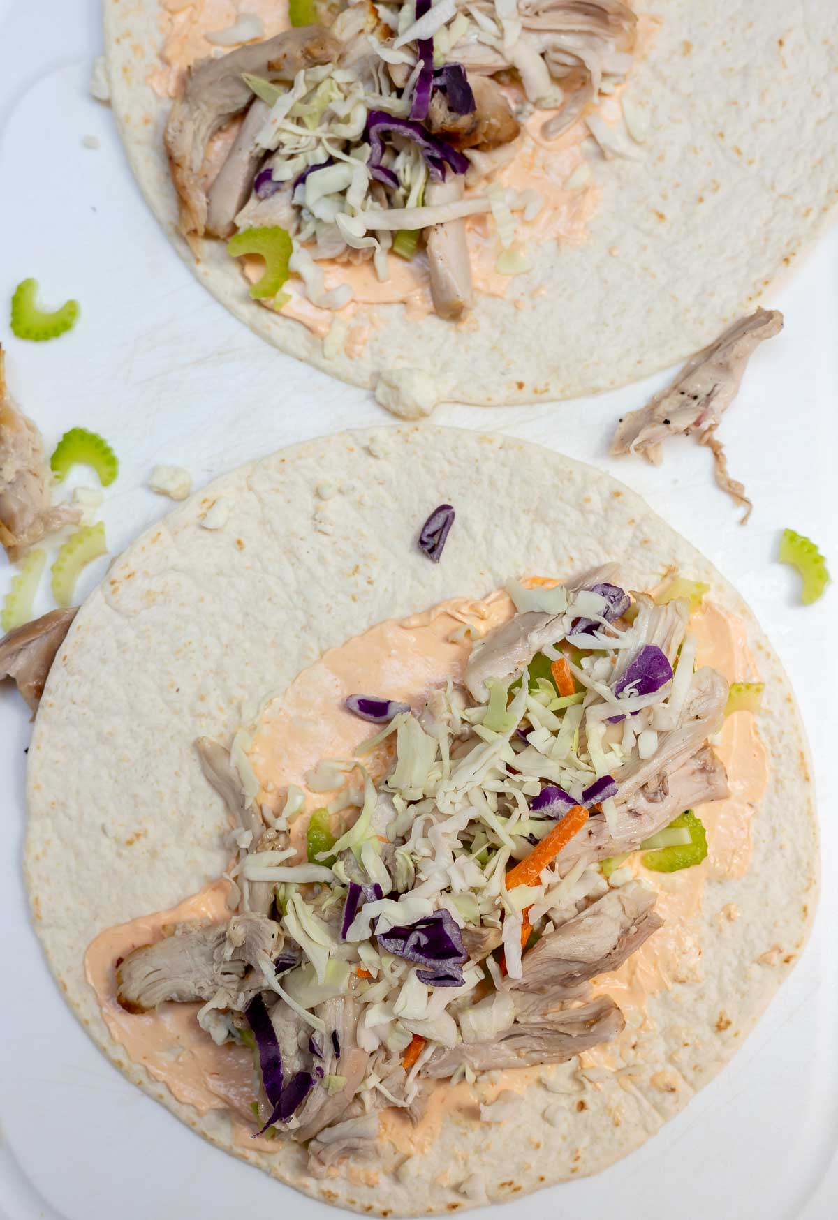 tortillas topped with cream cheese, chicken and cabbage on white cutting board