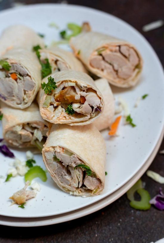 tortilla rolls filled with chicken, cream cheese and cabbage served on white plate