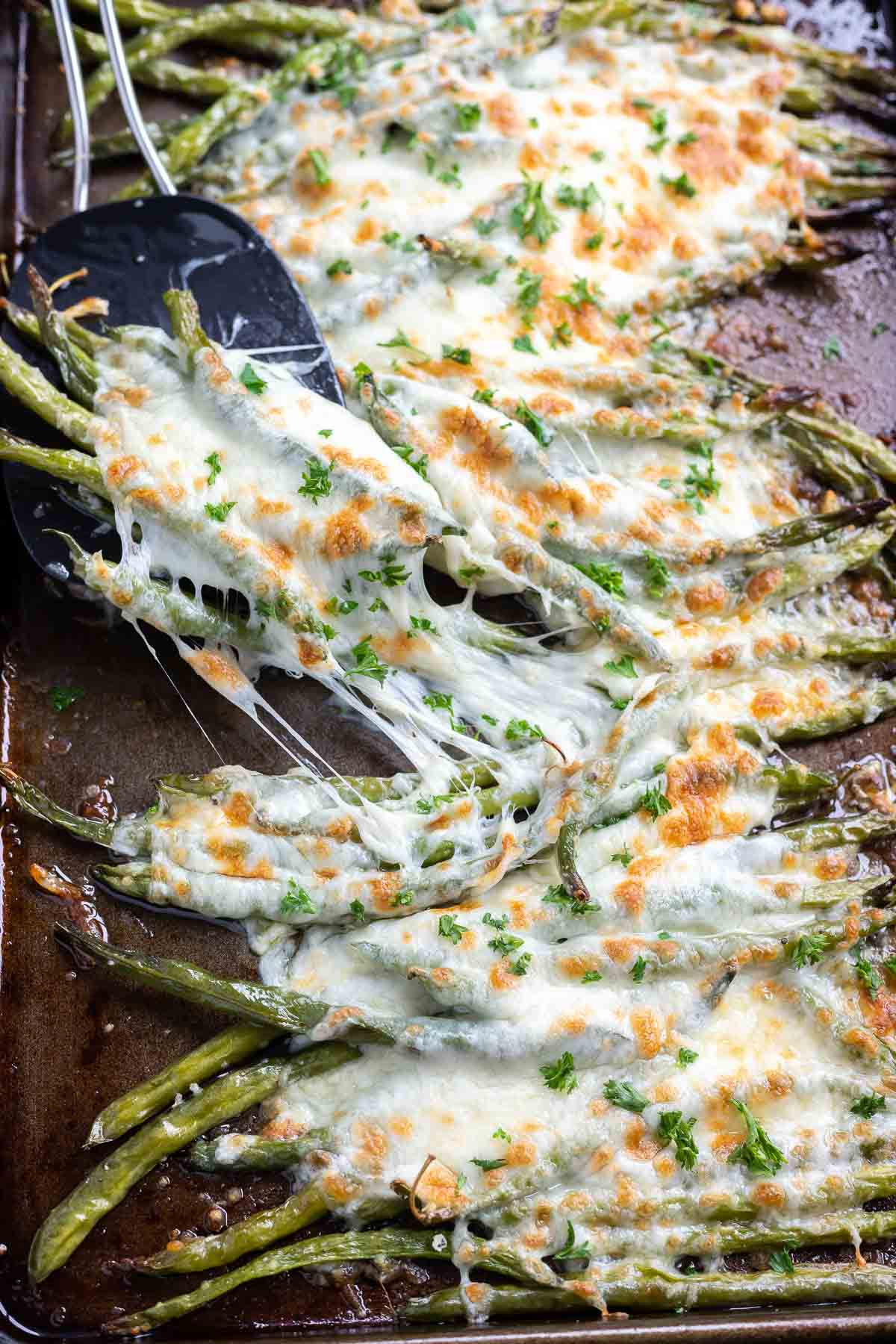 roasted cheesy green beans being lifted on spatula