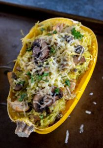 spaghetti squash filled with mushrooms, chicken, cheese and pesto