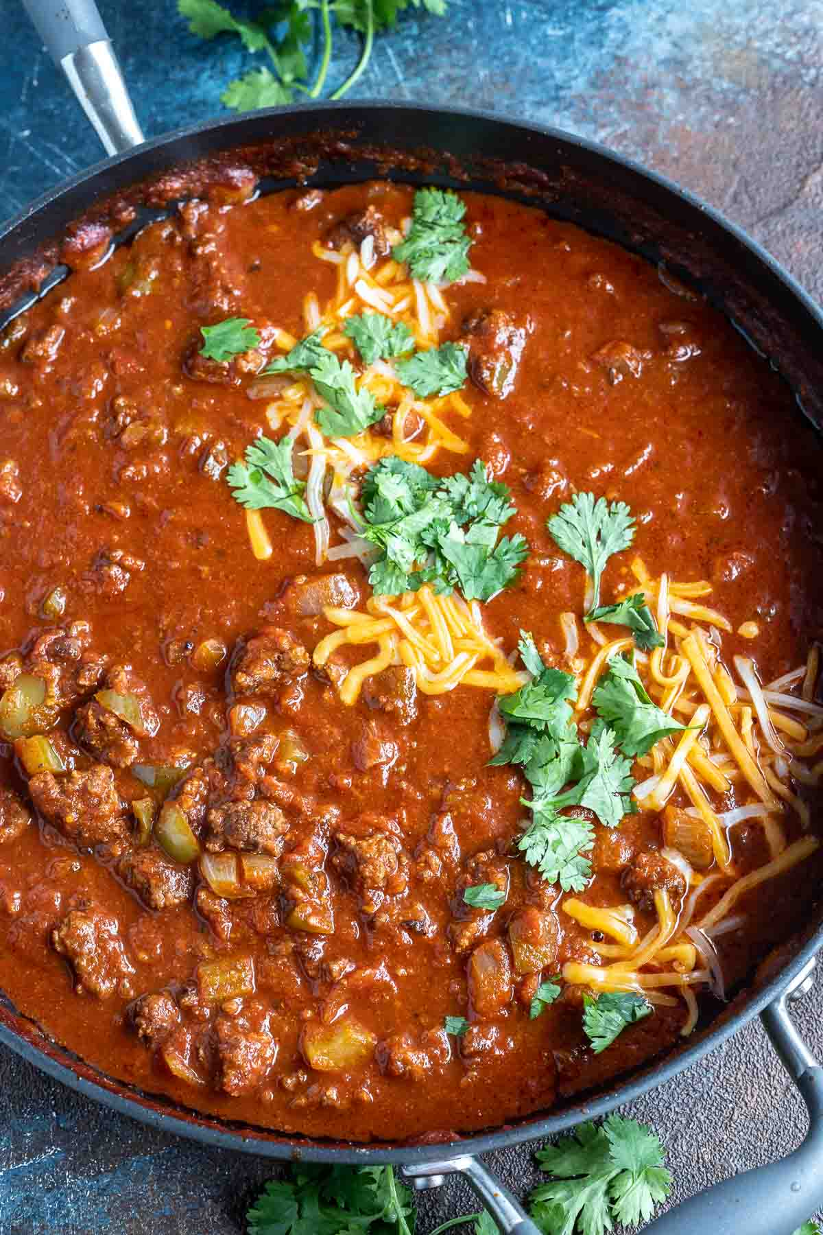 meat chili topped with shredded cheese and cilantro in skillet