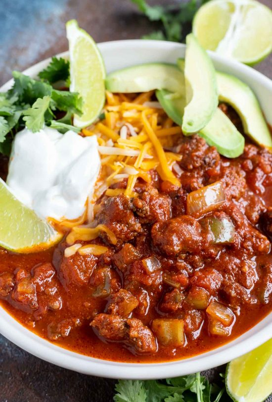 thick red chili topped with sour cream, cilantro and avocado in white bowl