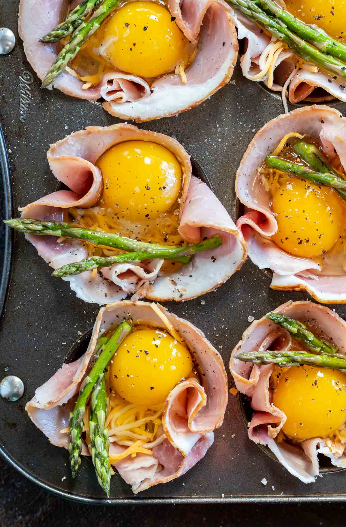 raw egg and asparagus spears added into muffin tins