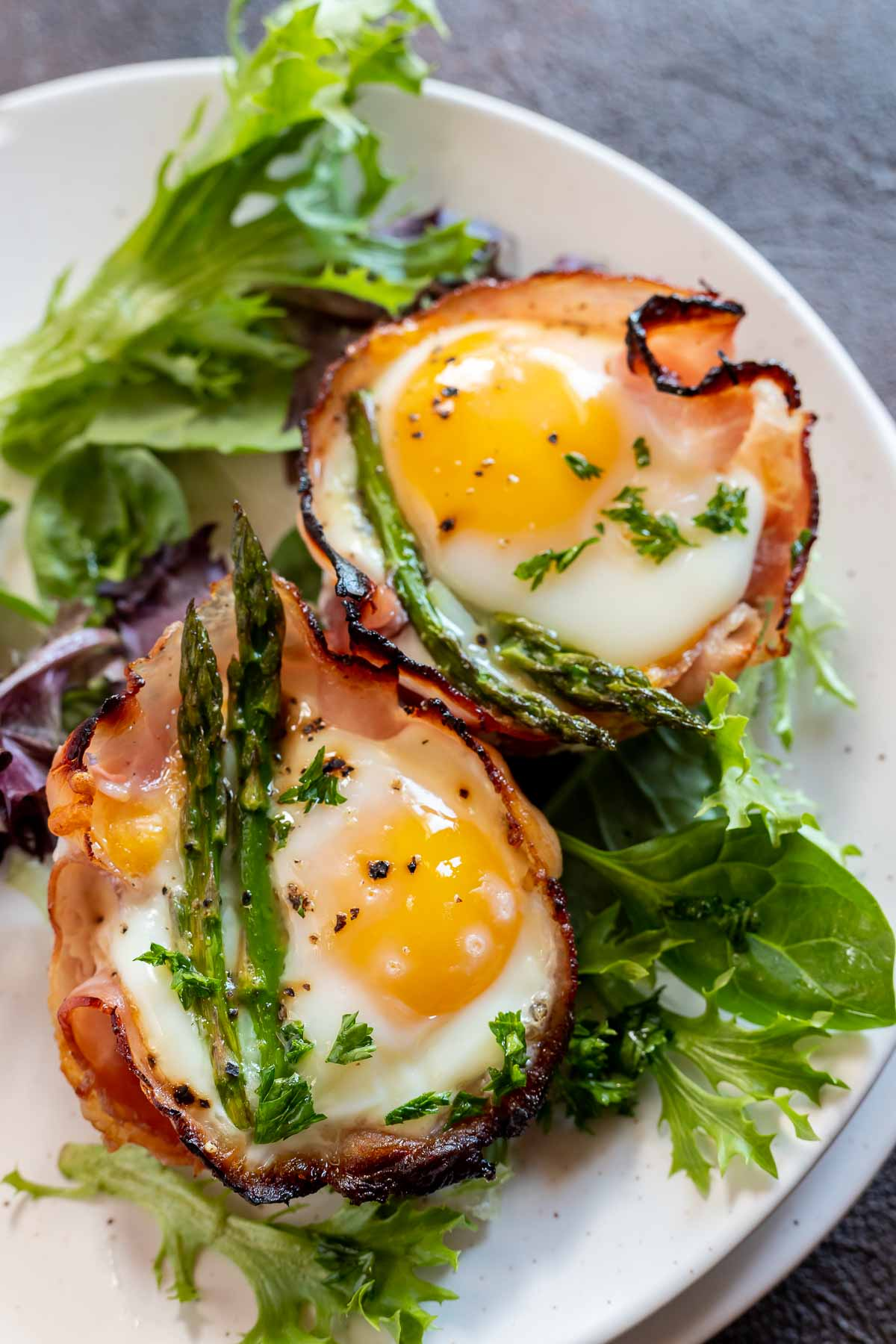 ham egg asparagus cups served with greens on white plate