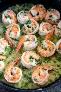 pink shrimp in buttery parsley sauce in pan