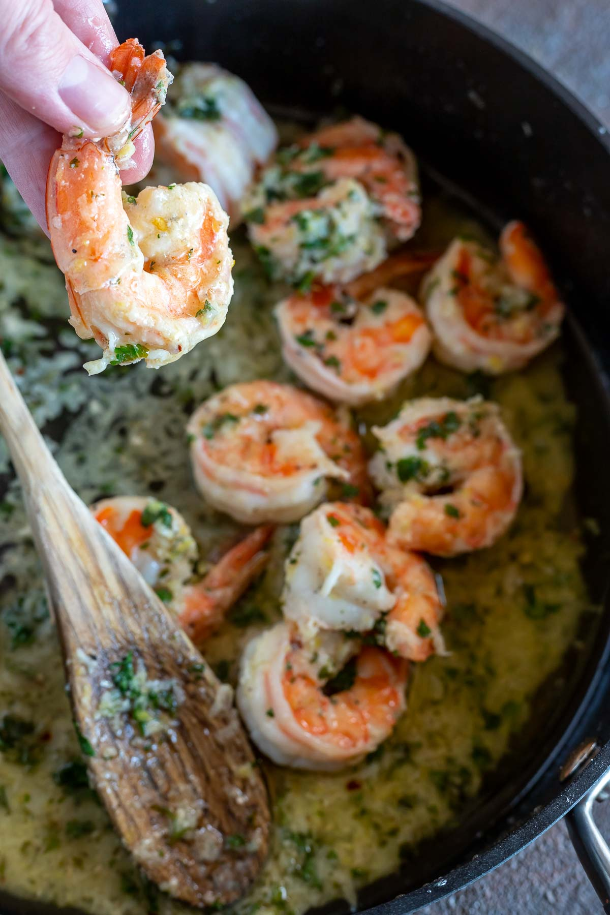 hand holding buttery shrimp above pan