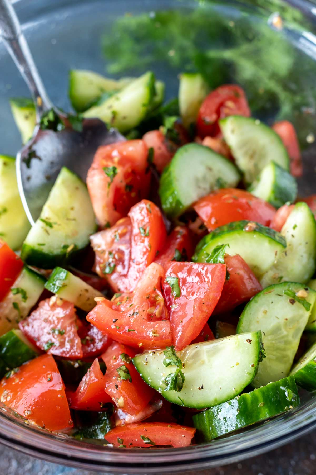 cucumber tomato salad in clear glass mixing bowl